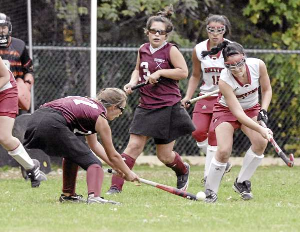 Foxcroft Academy's Rachel Cody (27) tries to work the ball into the circle past the defense of Dexter's Shelbee Lancaster (7) with players Gabi Henderson (13) of Foxcroft and Devyn Bell (15) of Dexter pursuing on the play in the second half of their game in Dexter Monday, Oct. 4, 2010. Bangor Daily News/Michael C. York
