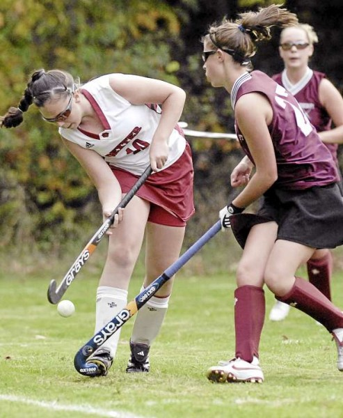 Dexter's Holly Libby (10) tries to work the ball over the stick of Foxcroft Academy's Rachel Cody (27) down the sideline in the second half of their game in Dexter Monday, Oct. 4, 2010. (Bangor Daily News /Michael C. York)