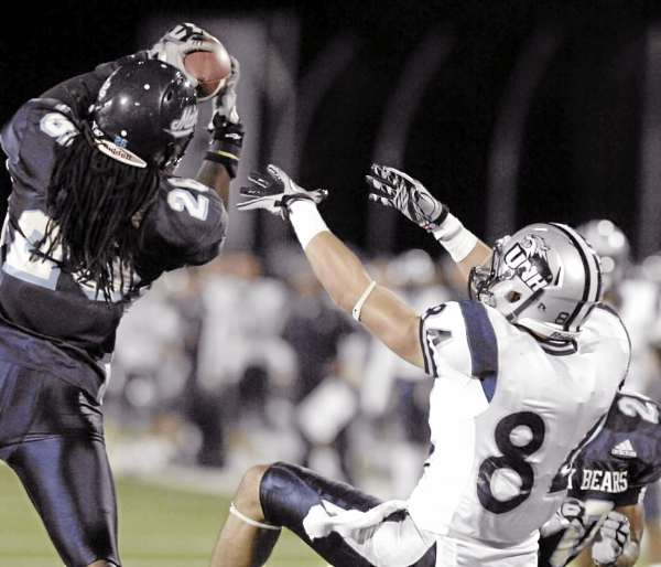 Maine defensive back Jerron McMillian (26) intercepts a pass intended for New Hampshire's Joey Orlando (84) in overtime  of their NCAA college football game  in Orono, Maine, Saturday, Oct. 2, 2010. (AP Photo/Michael C. York)
