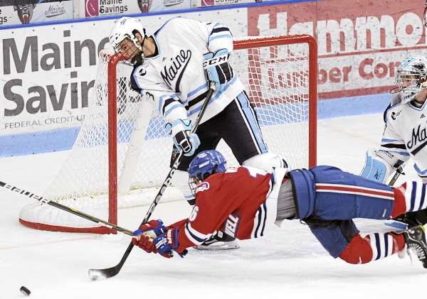 Maine defenseman Mark Nemec (3) sweeps the puck away from the empty net ahead of the diving Riley Wetmore (16) of the University of Massachusetts Lowell in the first period of their NCAA hockey game, Friday, October 8, 2010, in Orono, Maine. Maine won 8-2. (AP Photo/Michael C. York)
