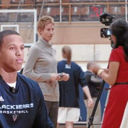 Gerald McLemore (left) of the University of Maine men's basketball team sits down for an interview with WABI-TV sports director Tim Throckmorton, while Black Bears women's coach Cindy Blodgett (second left, behind)) chats with reporter Melissa Kim of WLBZ-TV during Wednesday's UMaine basketball media day at the Memorial Gym in Orono.