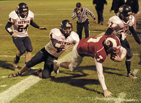 Bangor's Joe Seccareccia is knocked out of bounds by Brewer's  Brody Valley (4) while being pursued by Brewer's Adam Lufkin, #51, and Anthony Jackson,#17, during first-quarter action at Bangor on Friday night, October 22, 2010. (Bangor Daily News/Kevin Bennett)