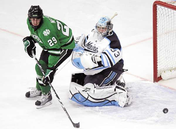 North Dakota's Brock Nelson (29) tries to direct a bouncing puck past Maine's goalie Shawn Sirman (33) in the first period of their NCAA  college hockey game, Friday, Oct. 22, 2010, in Orono, Maine. (AP Photo/Michael C. York)
