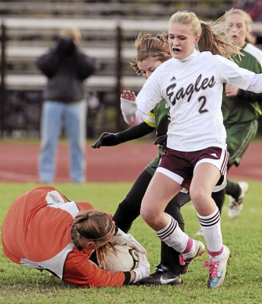 Old Town goalkeeper Annie Cashon (left) grabs the ball from the feet of Ellsworth's Katey Curtis during first-half action at Ellsworth on Friday, Oct. 22, 2010. Behind Curtis is Old Town's Micayla Hussey. Ellsworth won 1-0. (Bangor Daily News/Kevin Bennett)