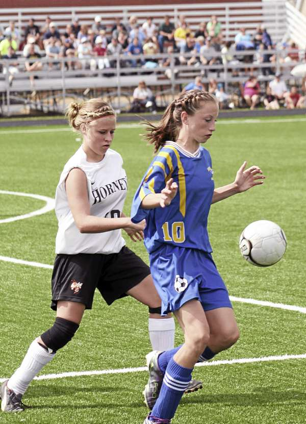 Washburn's Carsyn Koch (right) shields the ball from Brooke LaBelle of Ashland during a girls soccer game in Presque Isle in August. Koch is also becoming one of the state's top cross country runners as she won the Eastern Maine Class C individual title in Belfast Saturday. The Beavers are fielding a program for the first time in seven years. (Photo by Kevin Sjoberg)