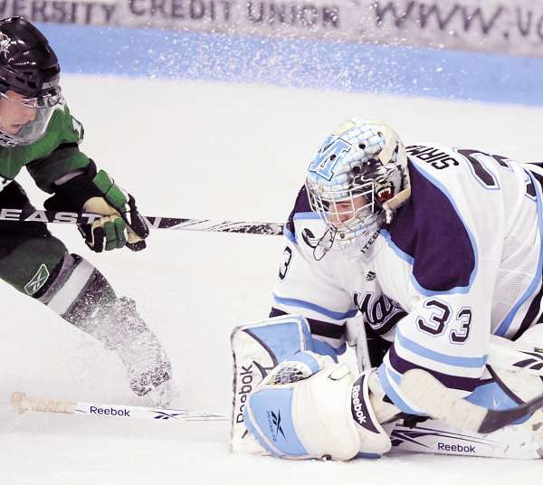 Maine's goalie Shawn Sirman (33) covers up the puck in a power play in the final minutes of the third period of their hockey game against North Dakota Friday night in Orono. Maine went on to win 7-3 and 4-2 on Saturday, a sweep sparked by a maintaining a simple approach and some line changes. (AP Photo/Michael C. York)