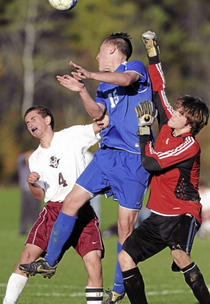 Orono's Daniel Perry, left, and Madawaska's Devin Pelletier and Madawaska goal keeper Kyle Blanchette collide during second-half action in a Class C quarterfinal Thursday, October 28, 2010 at Orono. Orono won 2-1. (BDN Photo by Kevin Bennett)