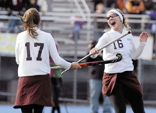 Foxcroft Academy's Tia Tondreau (16) and  Monica Miles (17) celebrate after scoring on their first penalty corner shot after double overtime in their state championship game against NYA in Orono, Saturday, Oct. 30, 2010. NYA won 2-1. BangorDailyNews/MichaelC.York