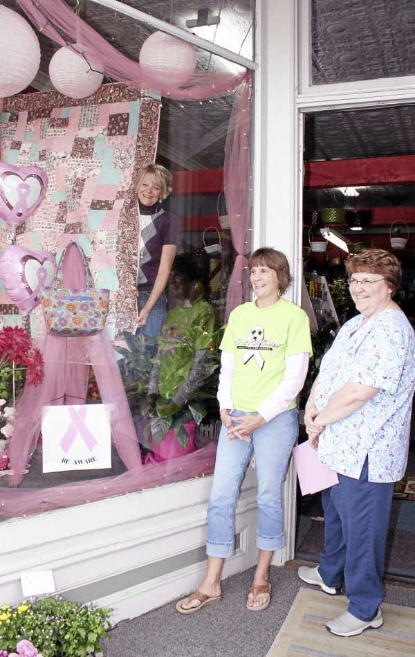 WINNING DESIGN - Karen Fitzpatrick, co-owner of Daniels Florist in Houlton?s Market Sq. shows off her window design to display a handmade quilt to raise money for the Bridge to Hope Breast Cancer Awareness Walk. Kim Folsom, center, is an organizer of the walk on Saturday, Oct. 16. Pam Hocking, right, created the quilt with her daughter and credits local quilters who assisted with finishing work. Houlton Pioneer Times Photo/Elna Seabrooks