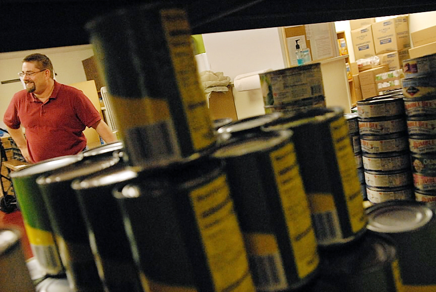 Seen through a  food cupboard shelf lined with canned goods, Paul Jerome talks with the BDN at the newly opened Brewer Christian Food Bank Wednesday, Sept. 29, 2010. Jerome is the president of the board of directors for this food bank. (Bangor Daily News/John Clarke Russ)