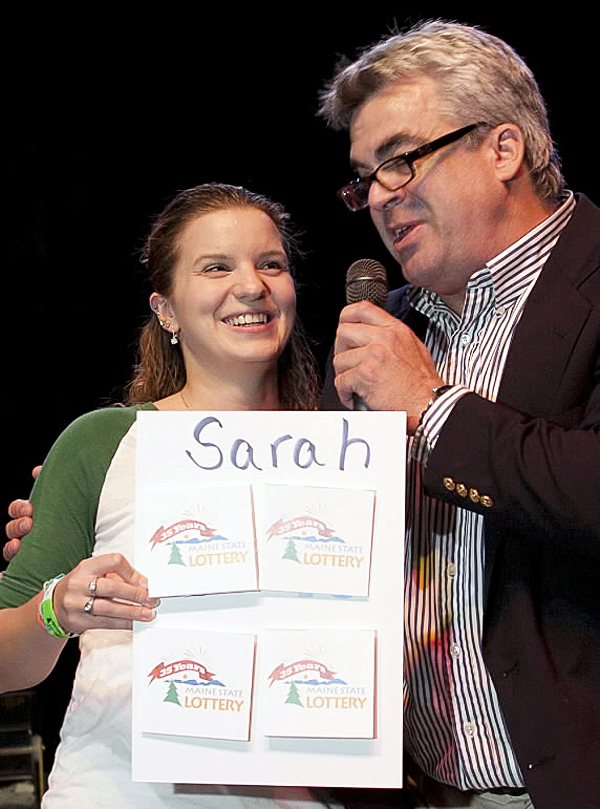 Sarah Cook (left), 23, learns she won $100,000 from Maine State Lottery anniversary host Barney Martin (right) during a live drawing in Augusta on Wednesday evening. (Photo courtesy of Maine State Lottery)