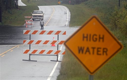 A man checks the depth of flood waters on Highway 133 in Leland, N.C., Thursday, Sept. 30, 2010. (AP Photo/Chuck Burton)