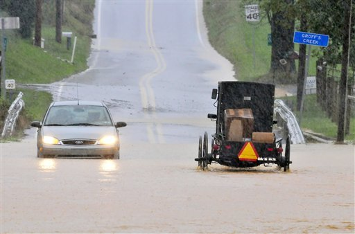 A buggy and car drive through high water on South Farmersville Road at Groff's Creek Thursday, Sept. 30, 2010 in Ephrata, Pa, Much of eastern Pennsylvania is under flood warnings as storms could bring as much as six inches of rain before leaving the area on Friday. The National Weather Service issued a tornado watch Thursday for counties stretching from Philadelphia west to York and north to Allentown. (AP Photo/Intelligencer Journal, Blaine Shahan)