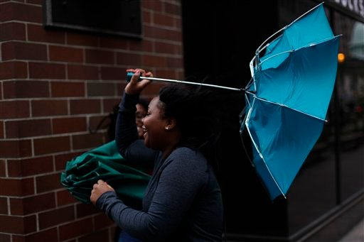 A woman's umbrella is turned inside out by a gust of wind in Philadelphia, Thursday, Sept. 30, 2010. A series of storms moving through Pennsylvania brought flooding that closed some roadways and prompted many schools to dismiss classes early. (AP Photo/Matt Rourke)