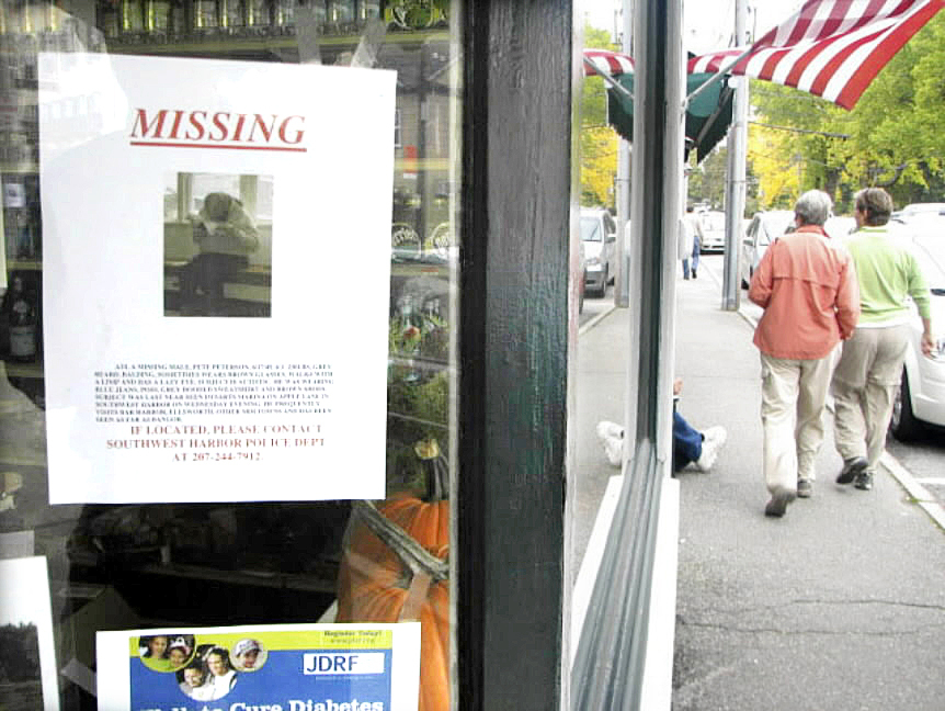Two pedestrians stroll Friday past a flyer about missing local resident Peter Peterson taped up in the window of Sawyer's Market in downtown Southwest Harbor. Peterson, who lives on his own and has been as described as possibly autistic, has not been spotted in the Mount Desert Island area for a week. BANGOR DAILY NEWS PHOTO BY BILL TROTTER 3 col max