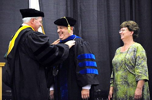 Robert Clark (center) smiles as he formally was inaugurated as the sixth president of Husson University and presented with the presidential medal by Arthur Fuller during a ceremony at the university Friday afternoon, October 1, 2010.  On the right is President Clark's wife, Tricia McGarry Clark. (Bangor Daily News/Gabor Degre)