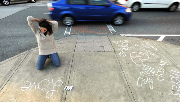 Adriana Hopkins of Bangor pulls her hair back as she creates positive chalk messages on the sidewalk on State Street in Bangor on Monday, October 4, 2010. Hopkins was joined by a dozen others inthe downtown area as they chalked up the sidewalks for the 2nd annual nation wide &quotYou-Are-Loved Chalk Message Project.&quot Monday was the first time Bangor has held the event. (Bangor Daily News/Kevin Bennett)