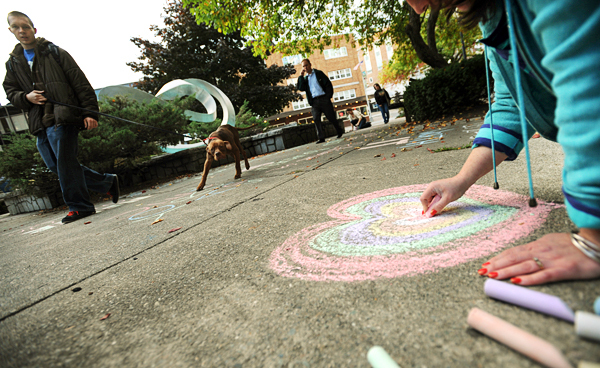 Carmen Montes, right, of Bangor creates a heart using chalk in West Market Square in Bangor on Monday, October 4, 2010. Montes was joined by a dozen others in the downtown area as they chalked up the sidewalks for the 2nd annual nationwide &quotYou-Are-Loved Chalk Message Project.&quot Monday was the first time Bangor has held the event. (Bangor Daily News/Kevin Bennett)