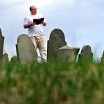 Walter Skold (left)  of Freeport, reads a Henry Wadsworth Longfellow poem while  in Eastern Cemetery in Portland last week. Skold has kicked off a 22-state tour to make Oct. 7 Dead Poets Remembrance Day.  (AP Photo/Robert F. Bukaty)