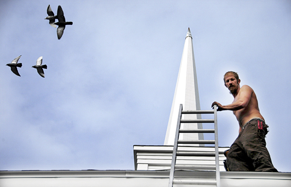 Peter Townshend, 27, of Bangor, a roofer at Roof Systems of Maine, was just about to start his climb down from a job atop the First Congregational Church of Lincoln at the end of the day on Monday when a flock of birds flew just overhead, startling him slightly. BANGOR DAILY NEWS PHOTO BY NICK SAMBIDES JR.