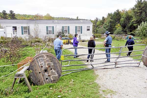 Local and state animal welfare personnel and a state trooper confer before six distressed horses were placed  inside a livestock trailer for removal from a property on Bald Mountain Road in Dedham Wednesday afternoon, October 6, 2010.  According to several local residents, the horses' owner has been away from the property for nearly a week, leaving the horses exposed to the elements and without much food. (Bangor Daily News/John Clarke Russ)