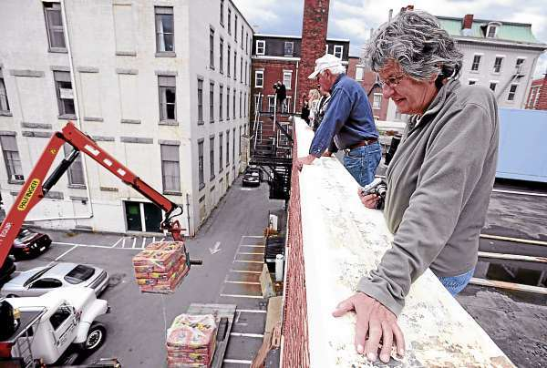 Gayle Crowley, right, and Charlie Taylor, center, look over the edge of the Hammond Street Senior Center as potting soil and lumber is lifted up for use in the &quotStill Growing&quot Rooftop Garden. Through their efforts,  the Hammond Street Senior Center has been awarded a $5,000 grant to expand their organic garden atop their building in downtown Bangor. (Bangor Daily News/Kevin Bennett)