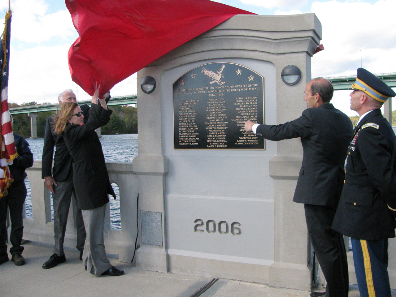 Tammy Lacher Scully and Gov. John Baldacci pull a red cover off the new bronze memorial plaque on Armistice Bridge in Belfast on Friday, Oct. 8 during the re-dedication ceremony. (Abigail Curtis/BDN)