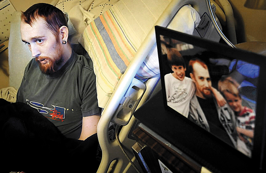 Anthony Napoleone lies in his bed on Thursday, Oct. 7, 2010, a picture of him with his sons Parish left and Gage (right) is seen in the foreground in Salina, Kan. Napoleone's dying wish is to go home to Maine and spend what time he has left with his children. ( Salina Journal, Jeff Cooper)
