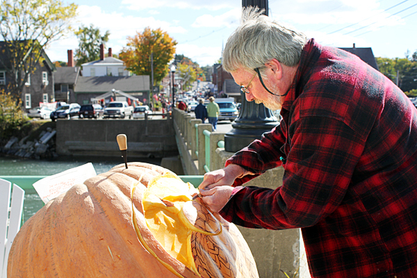 Tom Block, an art teacher at Wiscasset High School, volunteered to carve an owl out of a pumpkin Saturday at the Damariscotta Pumpkinfest. BANGOR DAILY NEWS PHOTO BY HEATHER STEEVES