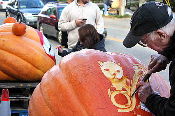 Ralph Moxcey of Bremen carves a Roman statuette of a cat out of a pumpkin at the Damariscotta Pumpkinfest on Main Street as Hannah Boone (background) paints her own pumpkin.    BANGOR DAILY NEWS PHOTO BY HEATHER STEEVES