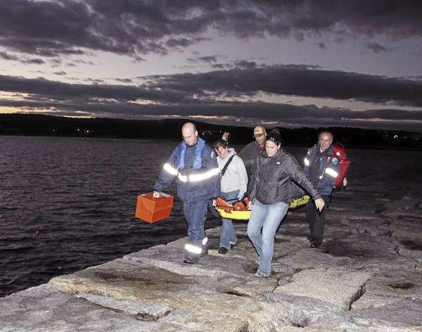 Firefighters Pat Lowe (from left) and Susan Simmons, Capt. Jeff Benner, firefighter Ellen Prosser and Lieutenant Dennis Camber carry an injured woman off the Rockland Breakwater Saturday.(Courtesy of Rockland Fire Department)