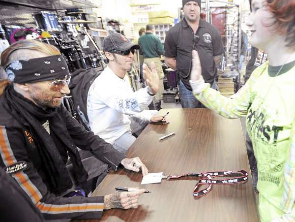 Erica Gordon of Orrington (right) high-fives with Godsmack singer Sully Erna while drummer Shannon Larkin signs her pass during an autograph session at Mark's Music in Brewer Sunday.  The band was the headliner of Smackfest in Bangor that featured a total of 18 bands Sunday. (Bangor Daily News/Gabor Degre)
