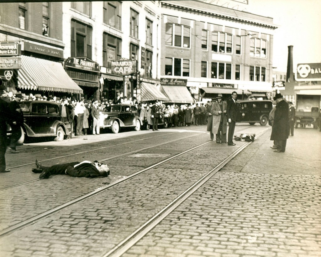 Shootout scene: Photo taken approximately 8:45 a.m. following the shooting deaths of &quotpublic enemy number one&quot Alfred Brady, 25 (foreground), and getaway car driver Clarence Lee Shaffer Jr., 21 (background). Head FBI agent Myron Gurnea, the tall man in black at right facing the camera, surveys the Central Street carnage. The other men are FBI agents, city officials, funeral home employees, and police officers. (Photo courtesy of Richard Shaw)