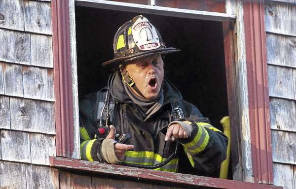 Bangor Fire Department Lieutenant Billy Van Peursem yells down some instructions from the second floor  during an early morning fire call at a home on Sidney Street early Wednesday morning, Oct. 13, 2010.   Photo by Monty J. Rand
