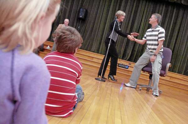 During a surprise school assembly at Vine Street School Thursday morning, Bangor Schools Supt. Betsy Webb congratulated Vine Street School physical education teacher Jason Pangburn, right,  after he was told he was a state teacher of the year award recipient.  On the left (in background) was Vine Street School Principal Tim McCluskey. (Bangor Daily News/John Clarke Russ)
