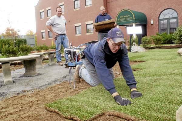 ORONO, ME -- OCTOBER 14, 2010 -- Ryan Whitmore lays sod while Todd Sheerman (CQ) carries another roll to be laid in the &quot2010 Traditions Garden&quot at the Buchanan Alumni House at the Universtiy of Maine on Thursday.  The 2010 class officers raised funds to have the garden made in honor of Alvin &quotAl&quot McNeilly '44 and the class of 1944.  Street's Landscape & Lawn Care, Inc of Alton put the garden in.  There will be a reception and ribbon cutting following the football game on Saturday. LINDA COAN O'KRESIK