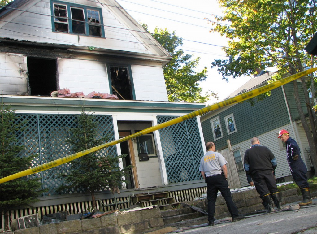 State investigators stand Wednesday outside a home on Roberts Square in Bar Harbor that caught fire late Tuesday night. One man who escaped from the burning house after a local police officer propped up a ladder for him to use was treated at a local hospital for smoke inhalation and a cut to his hand but later was released, according to the local fire chief. (Bangor Daily News/Bill Trotter)