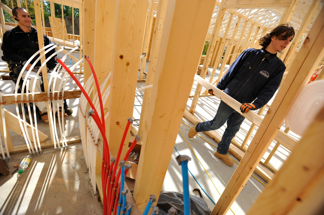 (BANGOR DAILY NEWS PHOTO BY JOHN CLARKE RUSS)  CAPTION  On Oct. 8, 2010, Michael Chasse (left), 28, watches Derek Michaud, right,  help his dad and uncle move roof trusses into position.  In March 2007, Chasse was paralyzed in a ski accident in Park City, Utah. Now he and is parents are building an energy-efficient,  handicap-accessible home not far from their existing home in Presque Isle. (Bangor Daily News/John Clarke Russ)