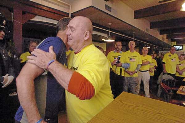 James Troutt (cq) of Sherman hugged Mike Ehredt, left, of Hope, Idaho after offering his gratitude during a special gathering for runner Mike Ehredt at the Tradewinds Motor Inn in Rockland Friday. Troutt is the grandfather of  fallen soldier Spc. Dustin Harris of Patten.  Since May, Ehredt ran about 4500 miles in honor of fallen soldiers. Minutes earlier,  Ehredt  finished his run at the Atlantic Ocean in Rockland.    (Bangor Daily News/John Clarke Russ)