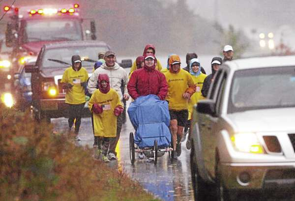 With a retinue of family members and supporters, Mike Ehredt, center, ran the final leg of his 4500-mile journey on Route 90 from West Rockport enroute to his run's terminus in Rockland Harbor late Friday morning, Oct. 15, 2010. Since May, Ehredt had run across the country to honor of fallen soldiers. He used the stroller to carry U.S. flags which planted in the roadside of every mile run.  (Bangor Daily News/John Clarke Russ)