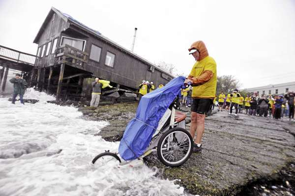 Mike Ehredt of Hope, Idaho dips the front wheel of his running stroller in the Atlantic Ocean at Rockland's harbor Friday morning marking the end of his approximately 4500-mile run to honor fallen soldiers. He used the stroller to carry U.S. flags which planted in the roadside of every mile run.  (Bangor Daily News/John Clarke Russ)