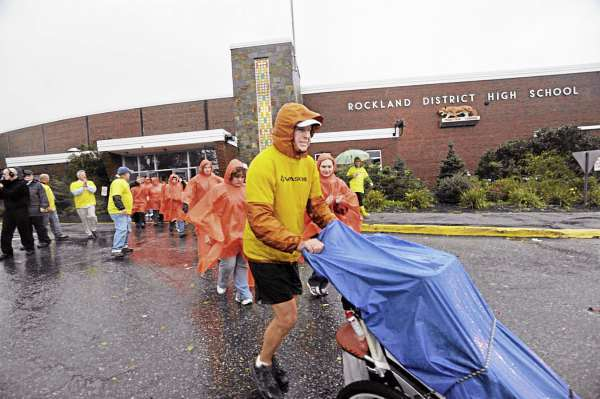 Mike Ehredt of Hope, Idaho departs Rockland High School after running with his flag stroller through the school hallway lined with supporters Friday morning, Oct. 15, 2010. Ehredt then finished the final leg of his 4500-mile run when he dipped his stroller into the Atalntic Ocean in Rockland Harbor late Friday morning. Since May, Ehredt had run about 4500 miles in honor of fallen soldiers. He used the stroller to carry U.S. flags which planted in the roadside of every mile run.  (Bangor Daily News/John Clarke Russ)