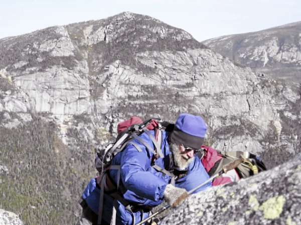 This unidentified hiker is climbing Katahdin on the Hunt Trail at around 3,500 feet. He's prepared for the severe conditions of fall by wearing a fleece hat, wool gloves and wind jacket. In the background is The Owl, elevation 3,736 feet. 10/16/10 story