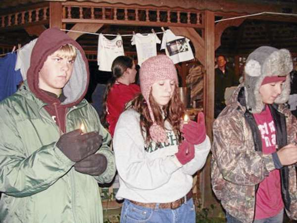 Dexter Regional High School students Erik Robinson (from left), Hayley Gross, and Hunter Belanger hold lighted candles at a domestic violence vigil held Saturday in Wayside Park in Dexter. The students were part of a contingent of students who later spent the night in the park to raise awareness for the homeless. (Bangor Daily News Photo by Diana Bowley)