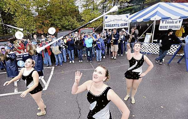 Foreground (left to right):  Junior Brandi Chadbourne of Saco, Megan Williams of Readfield, ME and Meagan Sawyer (cq) of Brewer, majorettes with the University of Maine Alumni Marching Band, showed off their baton skills for homecoming tailgaters before heading to Morse Field for the start of the U Maine-Villanova football game. (Bangor Daily News/John Clarke Russ)