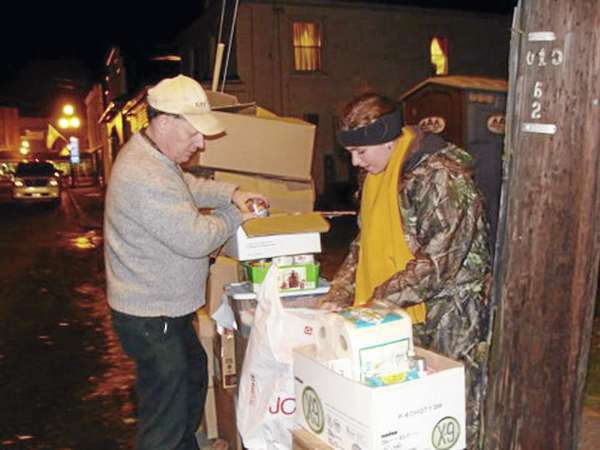 Dexter Regional High School Key Club advisor Rick Whitney and DRHS student McKenzie McKusick package food, blankets and tolietries donated Saturday night during ''Welcome to My Home,'' an annual event to raise awareness of the homeless. (Bangor Daily News Photo by Diana Bowley)