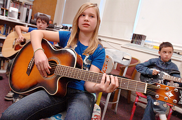 Mandy Cuskelly (front) and her Brewer Middle School fifth-grade classmates listen to teacher Robert Donnelly explain the parts of the guitar during their first guitar class Wednesday afternoon.  (BANGOR DAILY NEWS PHOTO BY JOHN CLARKE RUSS)