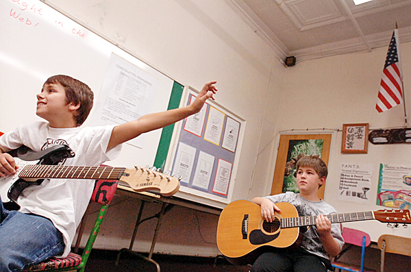 CAPTIONCaleb Winter, left,  eagerly raised his hand to name a guitar part for teacher Bob Donnelly during their first guitar class Wednesday afternoon, Oct. 13, 2010. Next to him was classmate Jacob Larochelle. Brewer Middle School and Brewer High School are offering rock and roll guitar classes, thanks to a grant from Stephen and Tabitha King. (Bangor Daily News/John Clarke Russ)   (WEB EDITION PHOTO)