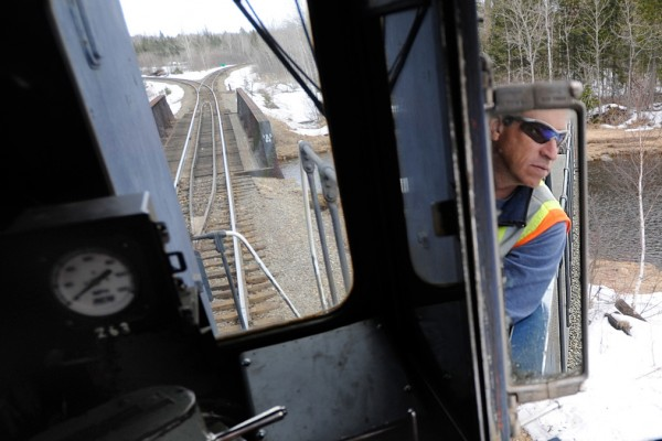 Engineer Rick Cameron of the Montreal, Maine and Atlantic railway looks at his rearview window as he reverses Engine 100 at the Squapan station in Masardis Thurdsday, March 18, 2010. Engine 100 was built in 1957.  Safety concerns and poor maintenance along sections of the MM&A railway in northern Maine sometimes limit the speed of their freight trains to 10 to 15 mph.  State officials are seeking a $25 million bond to repair rail in Aroostook, Penobscot and Androscoggin counties. Without such aid railways like MM&A might have to abandon their 241 miles of track which remain crucial to Maine industries. (Bangor Daily News/John Clarke Russ)