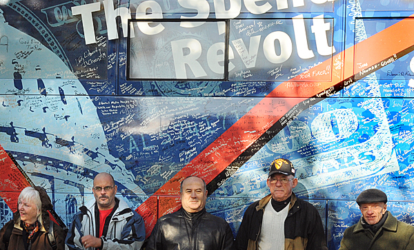 People pose in the front of the Spending Revolt bus in Paul Bunyan Park in Bangor for the first of three scheduled stops in Maine.  The tour started in July in Las Vegas, Nevada and protests government spending. Over the months people from all over the country signed the bus to show their support.   BANGOR DAILY NEWS PHOTO BY GABOR DEGRE